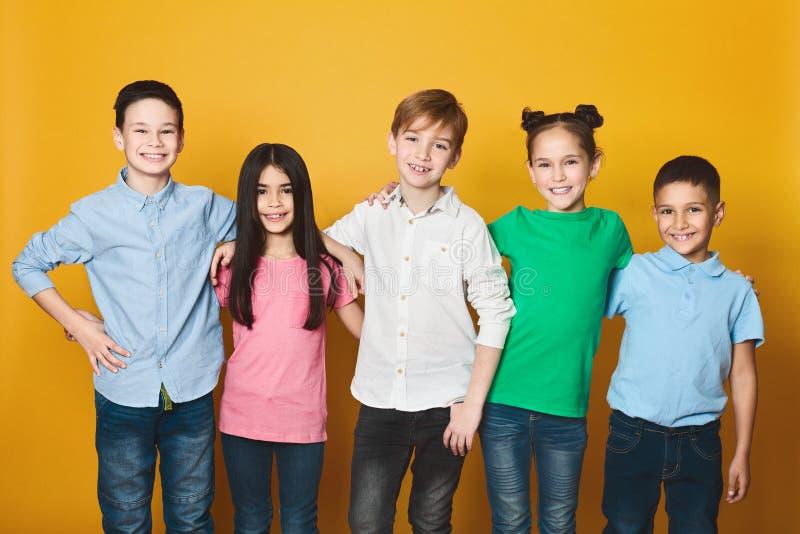 Grupp av ungar som står i rad som ser kameran arkivbild