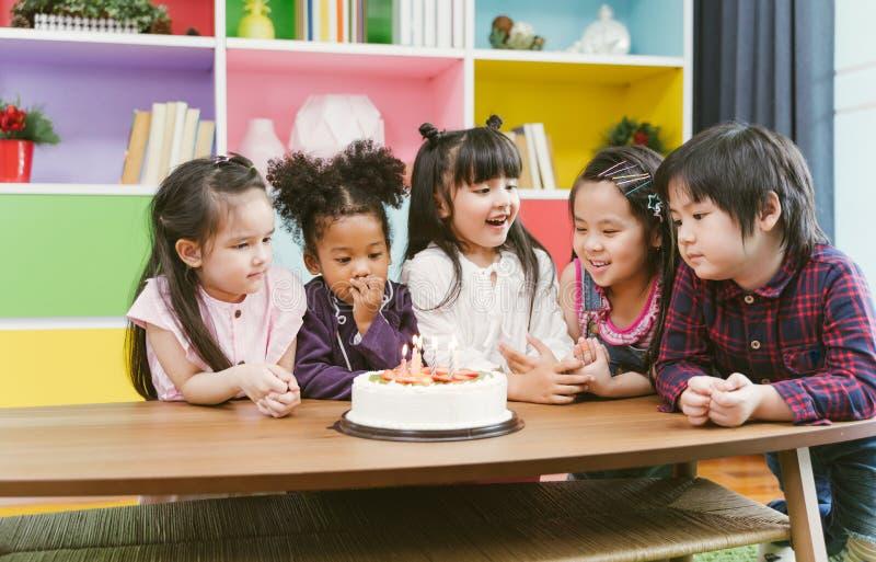 Grupp av ungar som tycker om ett födelsedagparti som ut blåser stearinljuset på kakan royaltyfria bilder