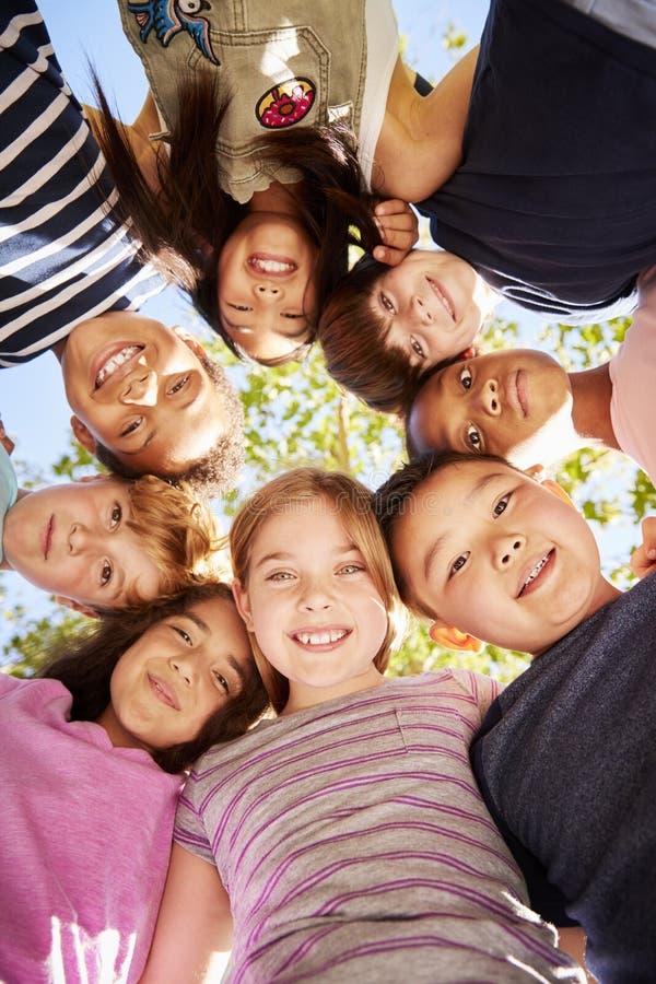 Grupp av ungar som utomhus ner ser på kameran, verticle royaltyfri bild