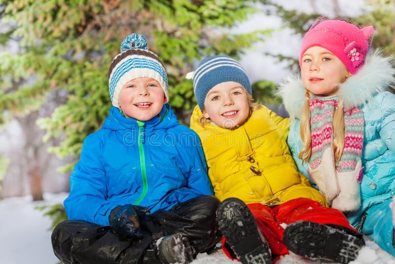 Grupp av ungar tillsammans i snön royaltyfria bilder