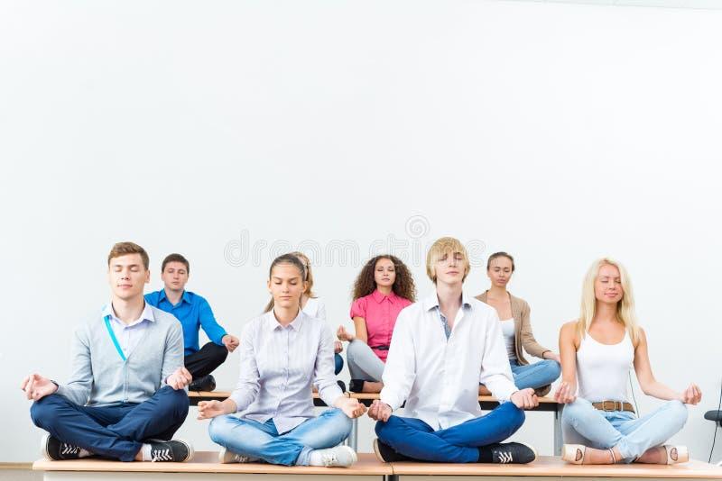 Grupp av ungdomaratt meditera royaltyfria foton