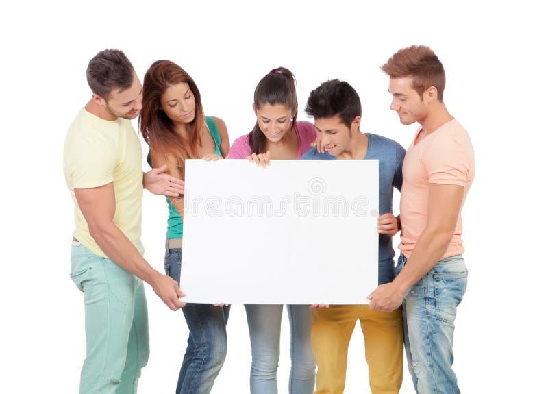 Grupp av ungdomarmed ett tomt plakat arkivfoto