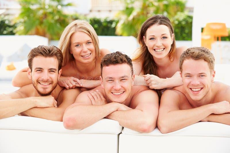 Grupp av ungdomarpå ferie som kopplar av vid simbassängen royaltyfri fotografi