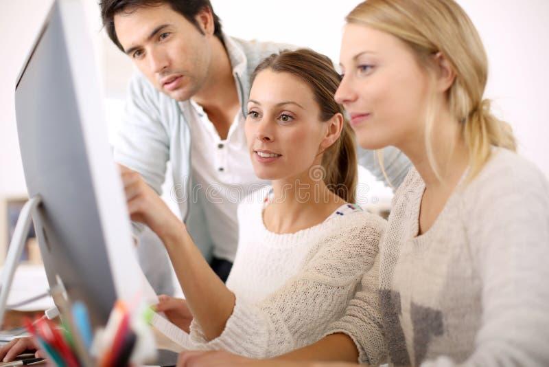 Grupp av ungdomarpå kontoret som arbetar på datoren fotografering för bildbyråer