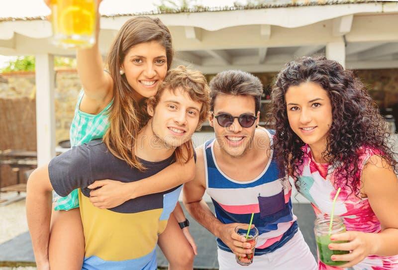 Grupp av ungdomarsom har gyckel i sommarparti arkivbild