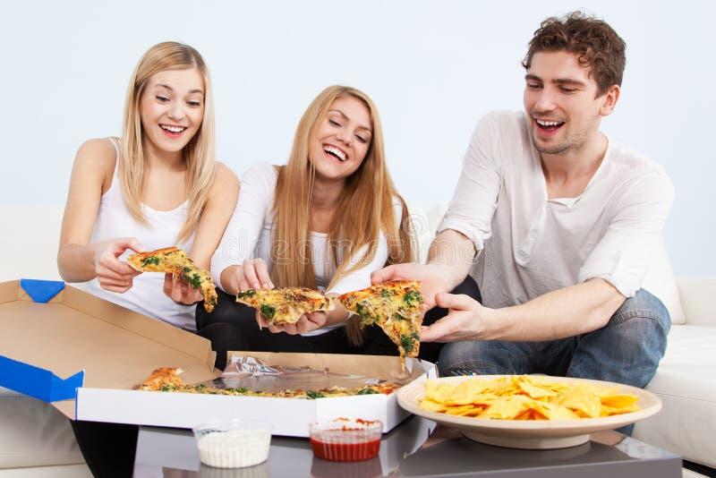 Grupp av ungdomarsom hemma äter pizza arkivfoton
