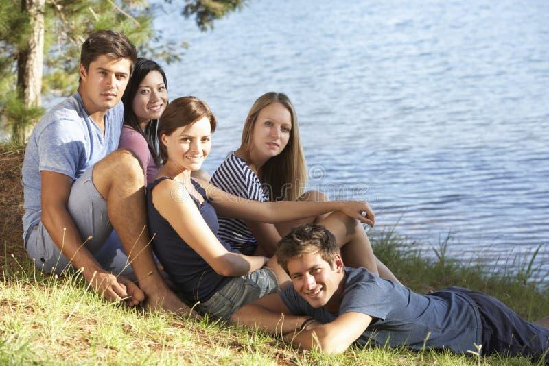 Grupp av ungdomarsom kopplar av på kusten av sjön royaltyfri fotografi