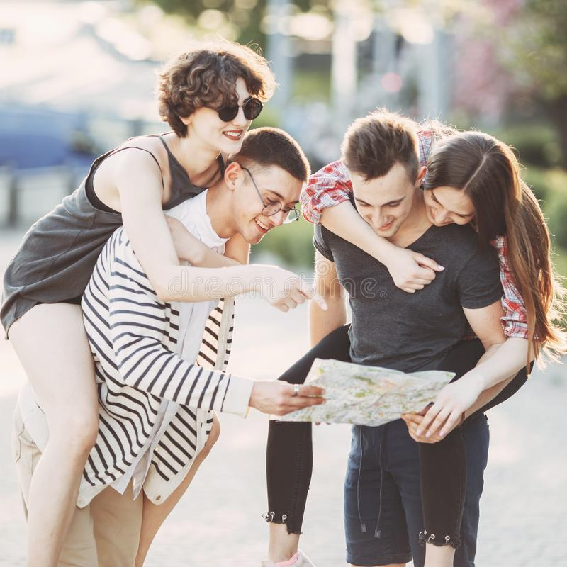 Grupp av ungdomarsom planerar semester genom att använda översikten arkivbild