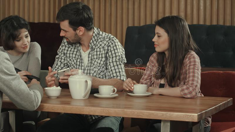 Grupp av ungdomarsom sitter på ett kafé, talar och dricker te royaltyfri foto