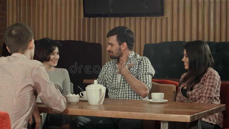 Grupp av ungdomarsom sitter på ett kafé, talar och tycker om arkivbilder
