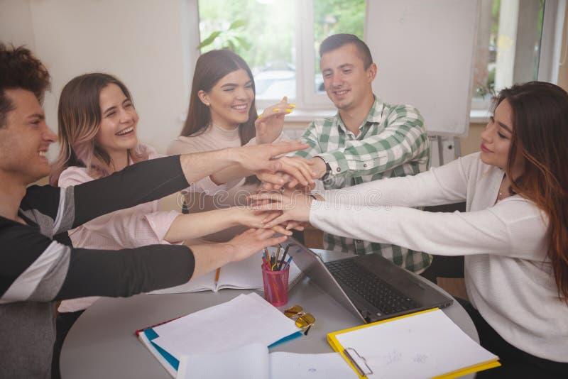 Grupp av ungdomarsom tillsammans studerar p? h?gskolaklassrumet arkivfoton