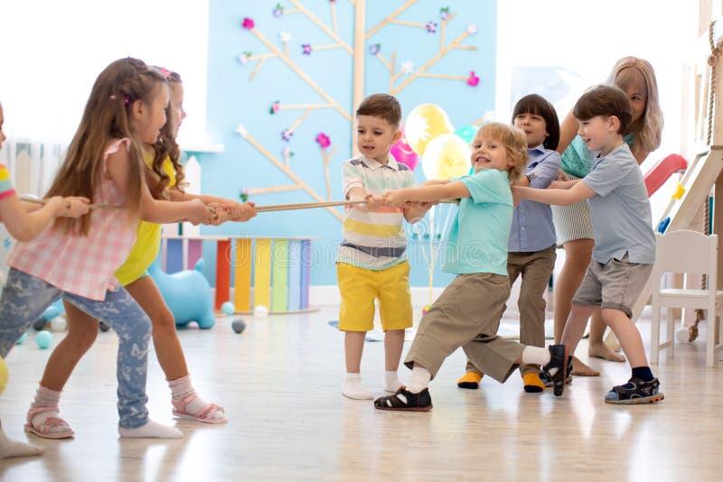 Grupp av ungelek och handtagrep tillsammans i daycare arkivbilder