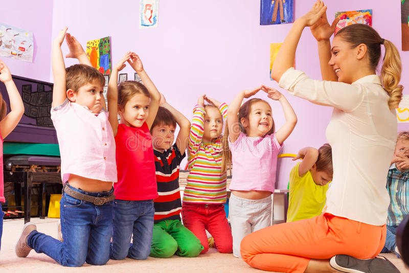 Grupp av ungerepetitiongesten efter läraren arkivfoton