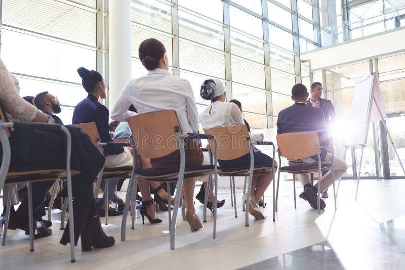 Grupp av ungt affärsfolk som lyssnar till affärsmannen i konferensrum royaltyfria bilder