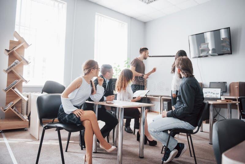 Grupp av ungt affärsfolk som tillsammans arbetar och meddelar i idérikt kontor arkivfoton
