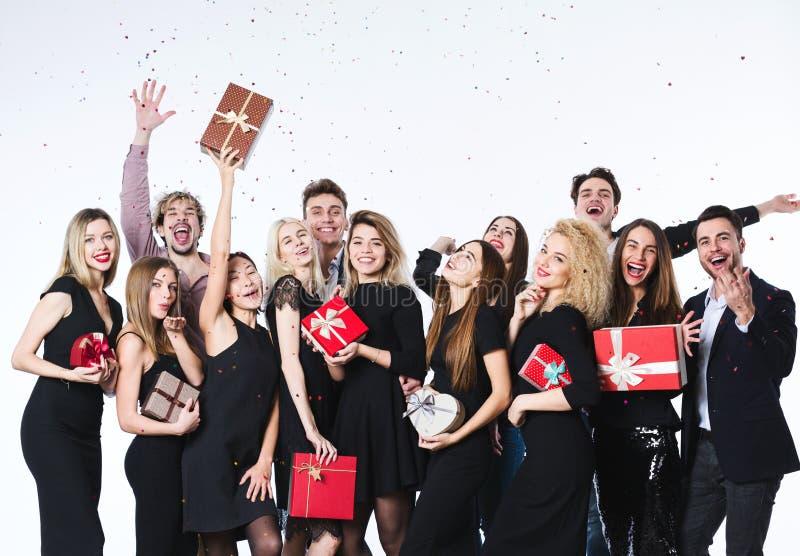 Grupp av ungt härligt folk i stilfull kläder med gåvaaskar i händer som har gyckel royaltyfri foto