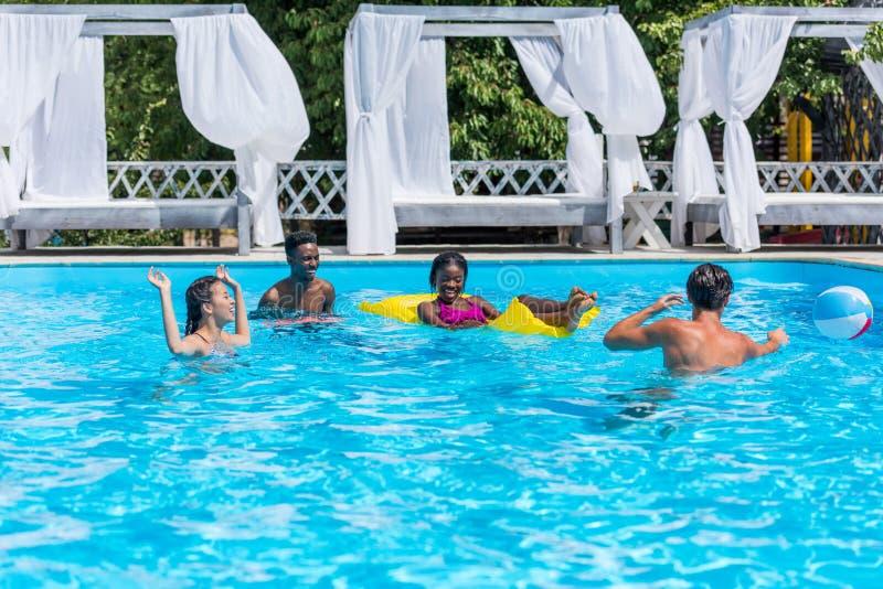 Grupp av ungt lyckligt multietniskt folk som har gyckel tillsammans i simning royaltyfri foto