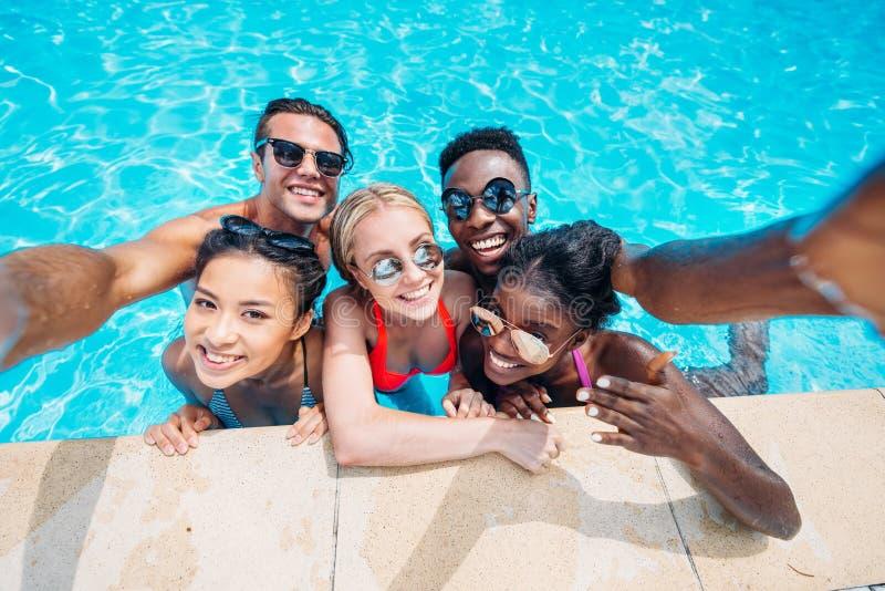 Grupp av ungt lyckligt multietniskt folk som tar selfie i simning royaltyfri foto