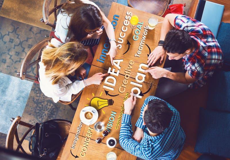Grupp av ungt och idérikt folk på tabellen som talar fotografering för bildbyråer