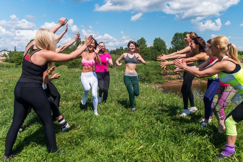 Grupp av upphetsade kvinnor som korsar finshlinen som en maratonspring på gräs- land parkerar in royaltyfria foton