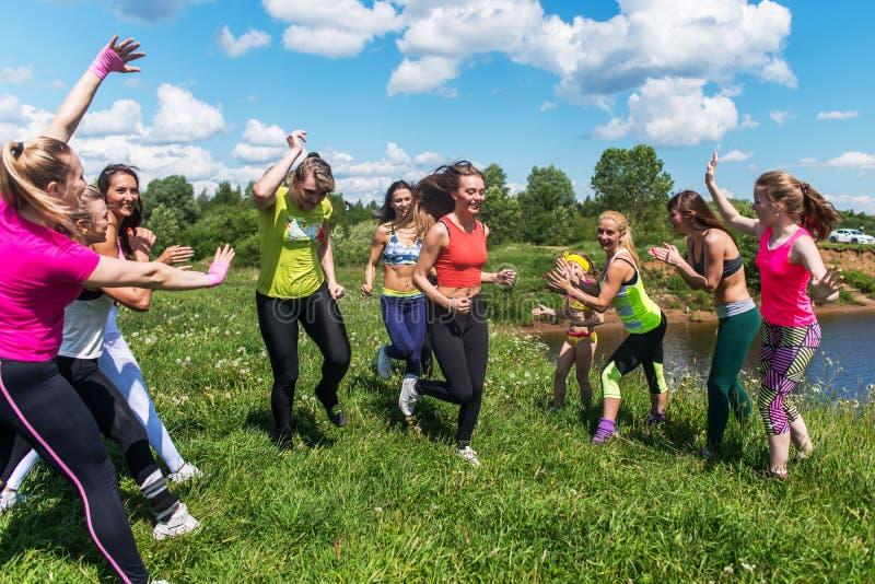 Grupp av upphetsade kvinnor som korsar finshlinen som en maratonspring på gräs- land parkerar in royaltyfri fotografi