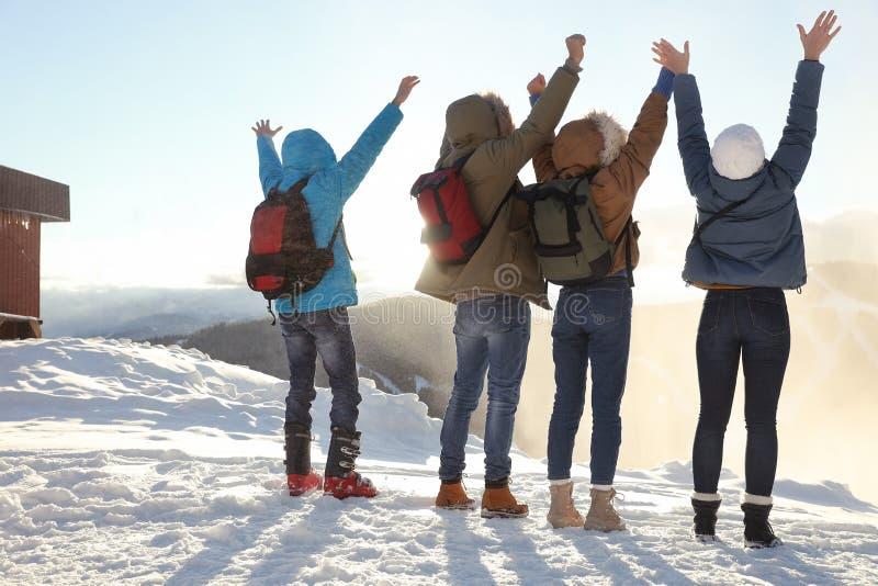 Grupp av upphetsade vänner med ryggsäckar som tycker om bergsikt under semester arkivfoton