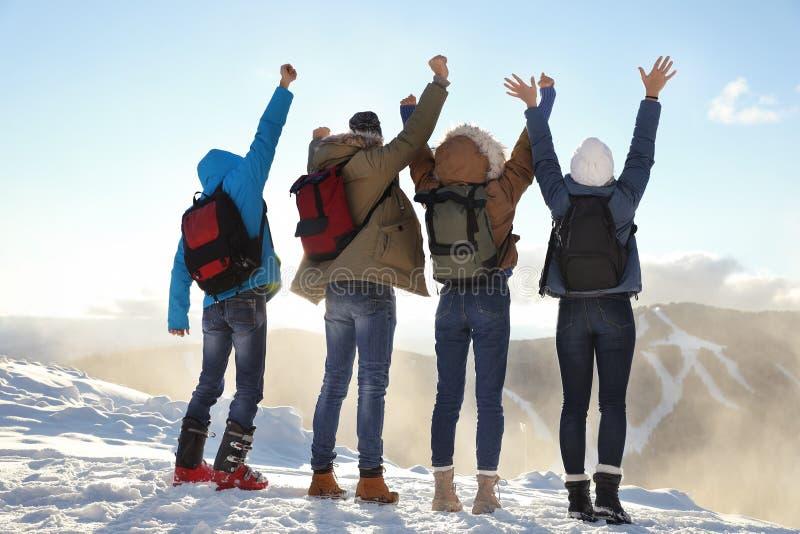 Grupp av upphetsade vänner med ryggsäckar som tycker om sikt under vintersemester arkivbild