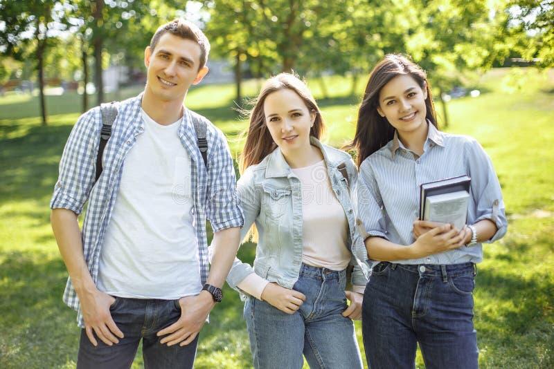 Grupp av utomhus- lyckliga högskolestudenter royaltyfria bilder