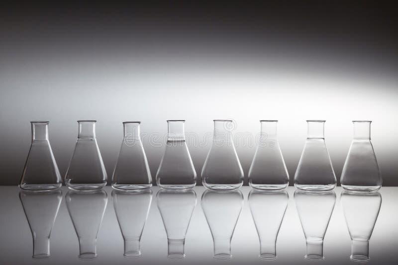 Grupp av utrustning för glasflaskor av vetenskapligt laboratorieglas på reflekterande yta royaltyfri fotografi
