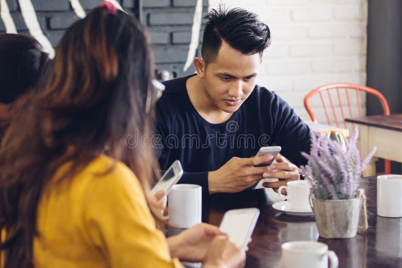 Grupp av vänner i kafé genom att använda mobiltelefoner royaltyfria foton