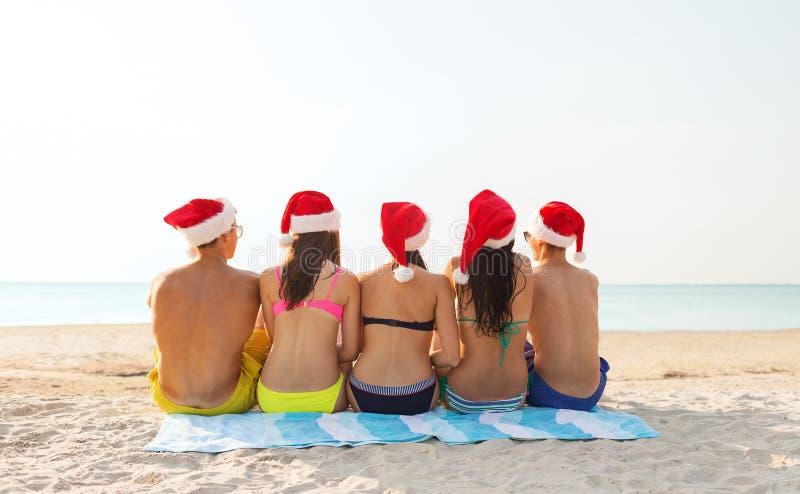 Grupp av vänner i santa hjälpredahattar på stranden royaltyfria bilder