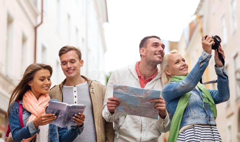 Grupp av vänner med den stadshandboken, översikten och kameran arkivfoton