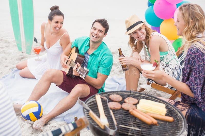 Grupp av vänner med drinkar och gitarrsammanträde bredvid en grillfest royaltyfri foto