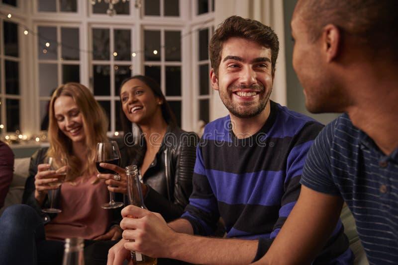 Grupp av vänner med drinkar som tillsammans tycker om huspartiet royaltyfri foto