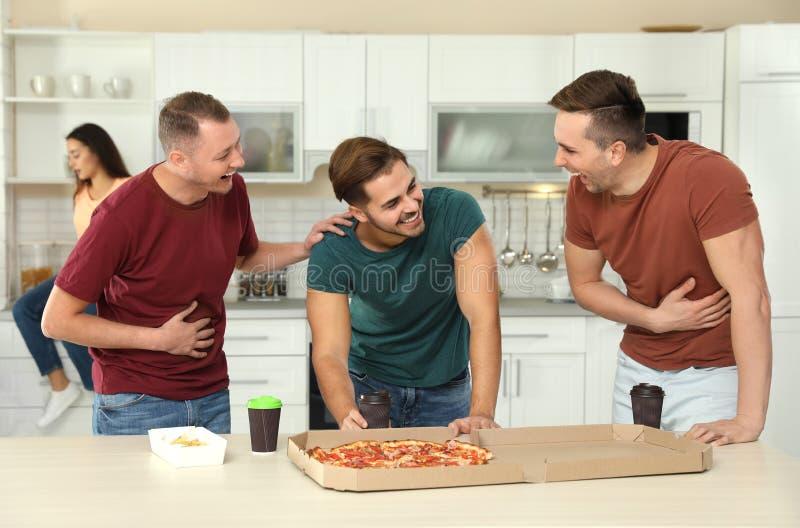 Grupp av vänner med smaklig mat som skrattar i kök royaltyfria bilder