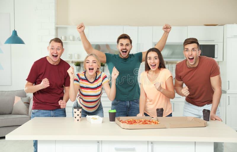Grupp av vänner med smaklig mat som tillsammans skrattar royaltyfri fotografi