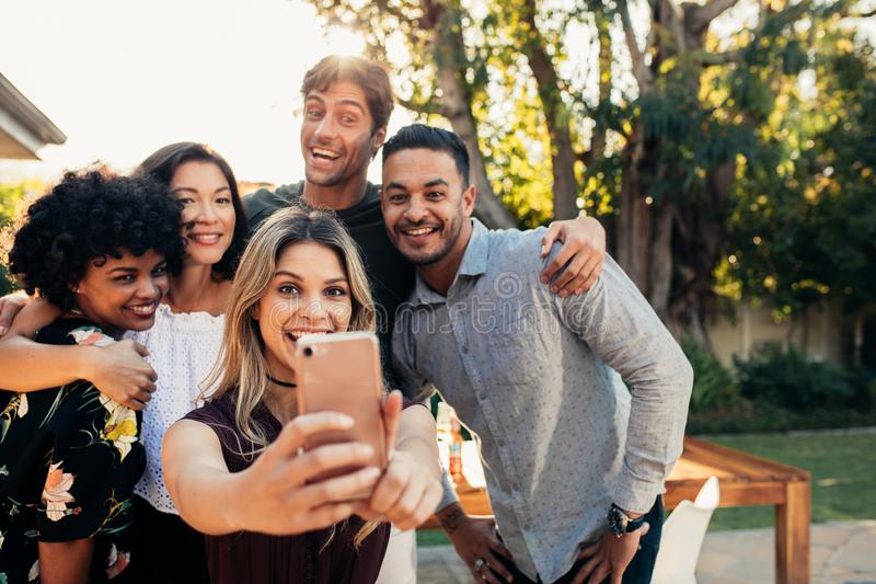 Grupp av vänner på det inflyttnings- partiet som tar selfie royaltyfri bild