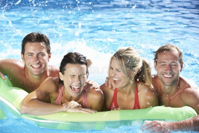 Grupp av vänner på ferie i simbassäng arkivfoton