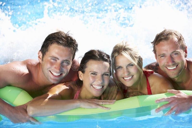 Grupp av vänner på ferie i simbassäng arkivfoto