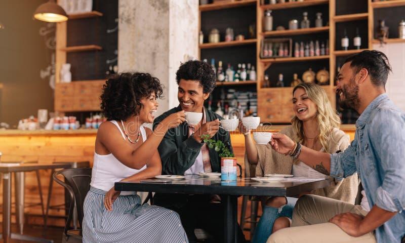 Grupp av vänner på kafét som har kaffe tillsammans royaltyfria foton