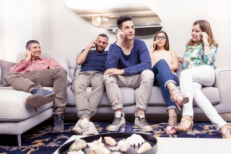 Grupp av vänner på soffan till telefonen samtidigt royaltyfri fotografi