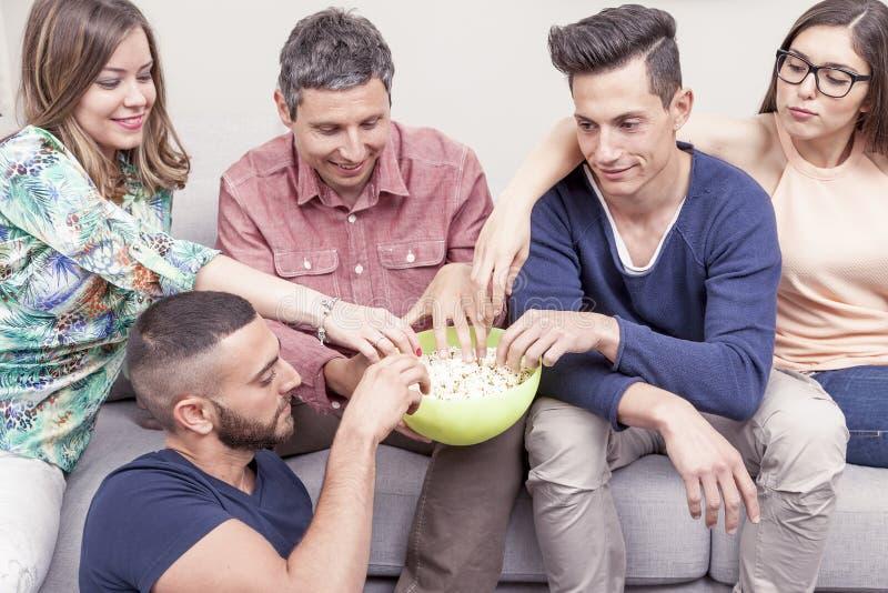 Grupp av vänner som äter popcorn på soffan royaltyfria foton