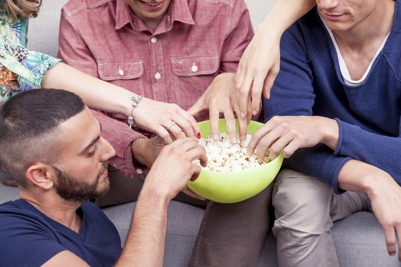 Grupp av vänner som äter popcorn på soffan royaltyfri bild
