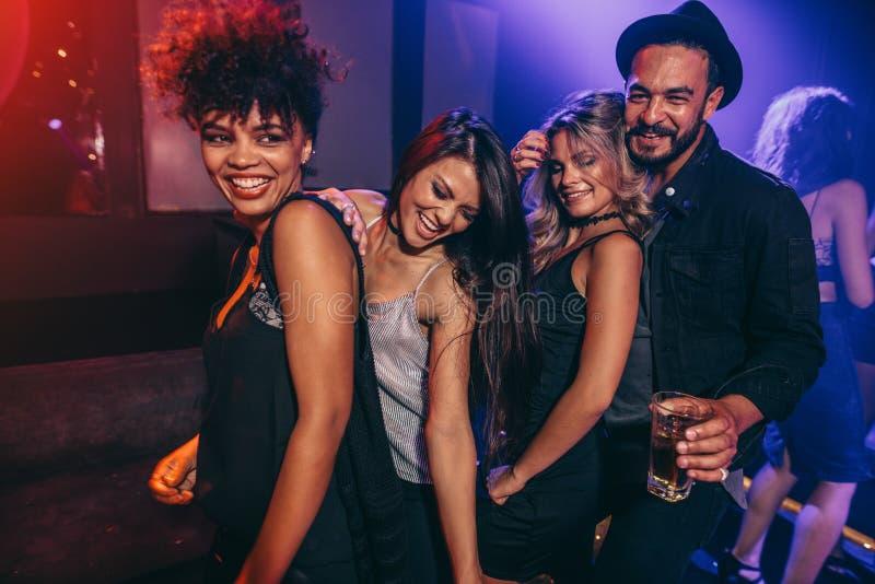 Grupp av vänner som dansar på diskoklubban arkivfoto
