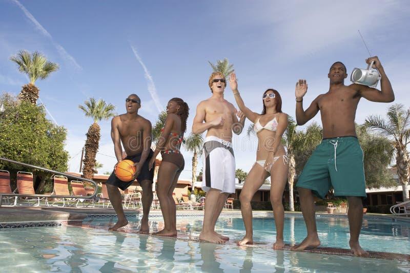 Grupp av vänner som dansar på poolsiden royaltyfria bilder
