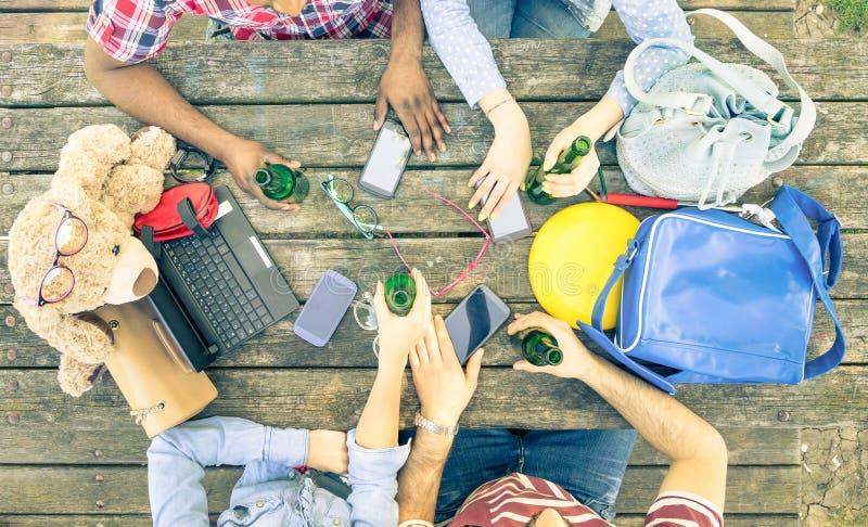 Grupp av vänner som dricker öl och använder smarta telefoner för mobil arkivbilder