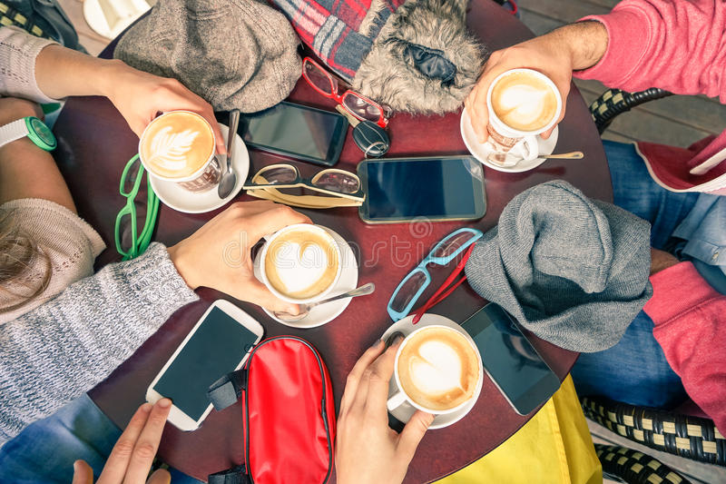 Grupp av vänner som dricker cappuccino på cafeteriarestauranger royaltyfri foto
