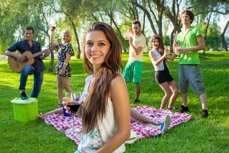 Grupp av vänner som festar i parkera royaltyfri foto