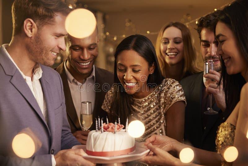 Grupp av vänner som firar födelsedag med det hemmastadda partiet royaltyfri bild
