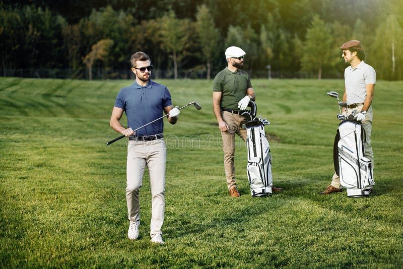 Grupp av vänner som går på golfbanan royaltyfri bild